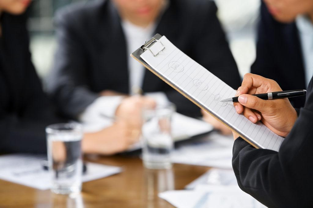 businesswoman's hand writing with other business people in background